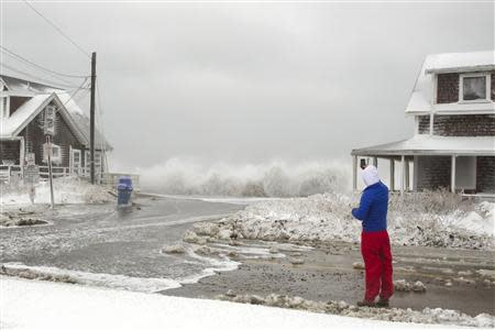 A man takes a cell phone photo of crashing waves during a winter nor'easter snow storm in Scituate, Massachusetts January 3, 2014. REUTERS/Dominick Reuter