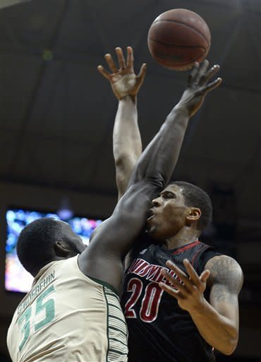 Louisville's Wayne Blackshear (20) is fouled by South Florida center Jordan Omogbehin (35) while going up for a shot during the first half of an NCAA college basketball game in Tampa, Fla., Sunday, Feb. 17, 2013. (AP Photo/Phelan M. Ebenhack)