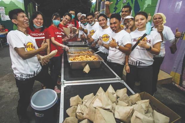 Hard Rock Cafe staff pack food with Kechara volunteers before distributing it to the homeless in conjunction with the restaurant's 25th anniversary celebration. ― Malay Mail pic