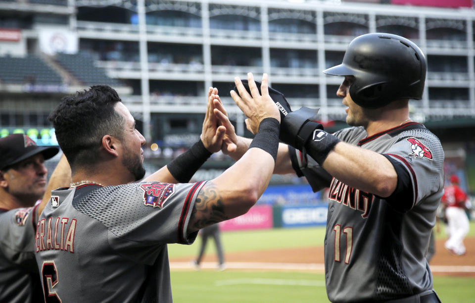 Arizona Diamondbacks A.J. Pollock (11) is congratulated by David Peralta (6) after scoring on an RBI double hit by Steven Souza Jr.,not pictured, during the first inning of a baseball game against the Texas Rangers, Monday, Aug. 13, 2018, in Arlington, Texas. (AP Photo/Brandon Wade)