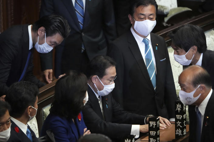 Japanese Prime Minister Fumio Kishida, center, and other lawmakers speak before dissolving the lower house, at an extraordinary Diet session at the lower house of parliament Thursday, Oct. 14, 2021, in Tokyo. Japan's new Prime Minister Kishida dissolved the lower house of parliament Thursday, paving the way for Oct. 31 national elections.(AP Photo/Eugene Hoshiko)