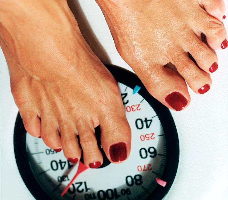 close up of a women's feet standing on a weight scale.