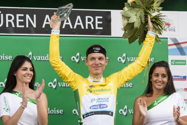 Overall leader German Tony Martin of team Omega Pharma Quick Step celebrates with his yellow jersey on the podium during the 5th stage, a 183,6 km race from Ossingen to Bueren an der Aare, at the 78th Tour de Suisse UCI ProTour cycling race, in Bueren an der Aare, Switzerland, on Wednesday, June 18, 2014. (AP Photo/Keystone,Jean-Christophe Bott)