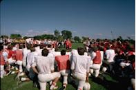 <p>A high school football team takes a knee while listening to presidential hopeful Walter Mondale give a speech.</p>