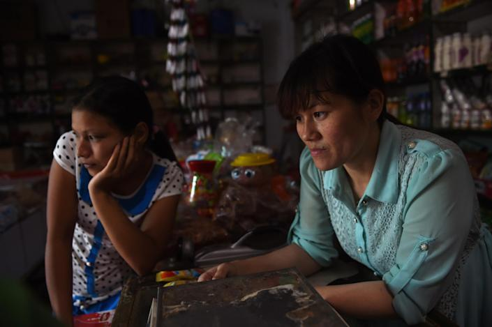 Vietnamese bride Nguyen Thi Hang (R) and fellow Vietnamese bride Vu Thi Hong Thuy in the shop where Hang works in Weijian village, China's Henan province on July 29, 2014 (AFP Photo/Greg Baker)