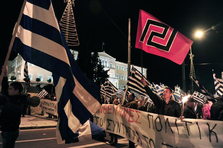-Supporters of the ultra nationalist party Golden Dawn shout slogans and wave Greek national flags and their party's flags as they demonstrate outside the parliament in Athens on November 30, 2013