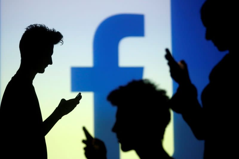 FILE PHOTO: People pose with mobile devices in front of projection of Facebook logo in this picture illustration taken in Zenica