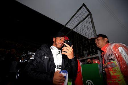 Formula One - F1 - Chinese Grand Prix - Shanghai, China - 7/4/17 - Mercedes driver Lewis Hamilton of Britain uses his phone at the Shanghai International Circuit. REUTERS/Aly Song