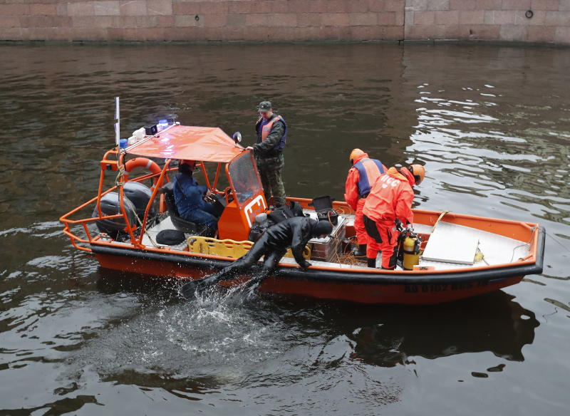 Rescuers examine the bottom of the Moika River.