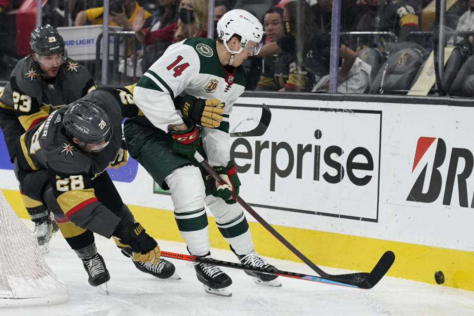 Vegas Golden Knights left wing William Carrier (28) vies for the puck with Minnesota Wild center Joel Eriksson Ek (14) during the third period of an NHL hockey game Monday, May 24, 2021, in Las Vegas. (AP Photo/John Locher)