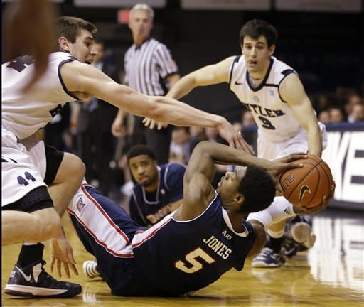 Butler center Andrew Smith, left, and guard Alex Barlow, back right, defend Duquesne guard Jerry Jones (5) during the first half of an NCAA college basketball game in Indianapolis, Tuesday, Feb. 19, 2013. (AP Photo/Michael Conroy)