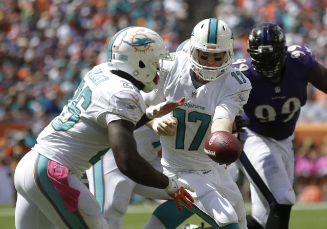 Miami Dolphins quarterback Ryan Tannehill (17) hands the ball to Miami Dolphins running back Lamar Miller (26) during the first half of an NFL football game against the Baltimore Ravens, Sunday, Oct. 6, 2013, in Miami Gardens, Fla. (AP Photo/Wilfredo Lee)