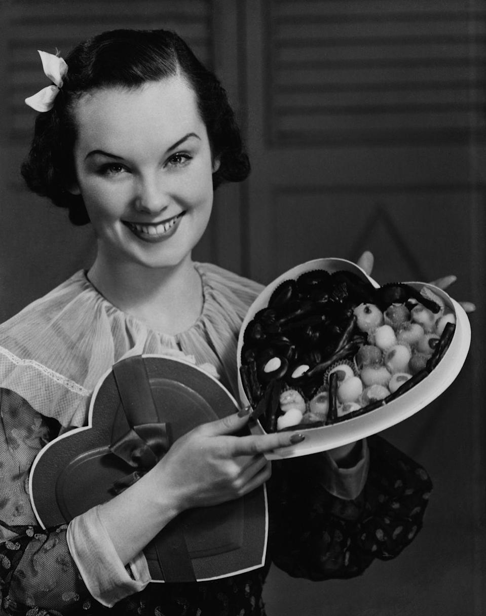 <p>A model poses with a Valentine's Day staple, the traditional heart-shaped box of chocolate. </p>