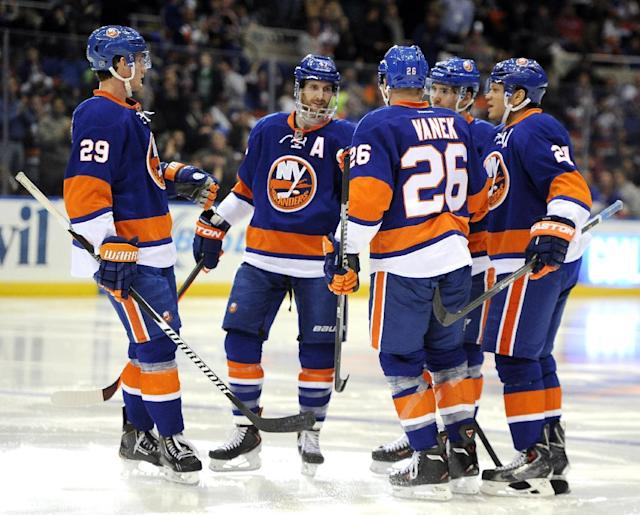 New York Islanders', from left, Brock Nelson (29), Andrew MacDonald, Thomas Vanek (26), John Tavares and Kyle Okposo (21) celebrate Okposo's goal against the Tampa Bay Lightning in the second period of an NHL hockey game on Tuesday, Dec. 17, 2013, in Uniondale, N.Y. (AP Photo/Kathy Kmonicek)