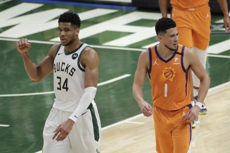 Milwaukee Bucks forward Giannis Antetokounmpo (34) celebrates in front of Phoenix Suns guard Devin Booker (1) at the end of Game 4 of basketball's NBA Finals Wednesday, July 14, 2021, in Milwaukee. (AP Photo/Aaron Gash)