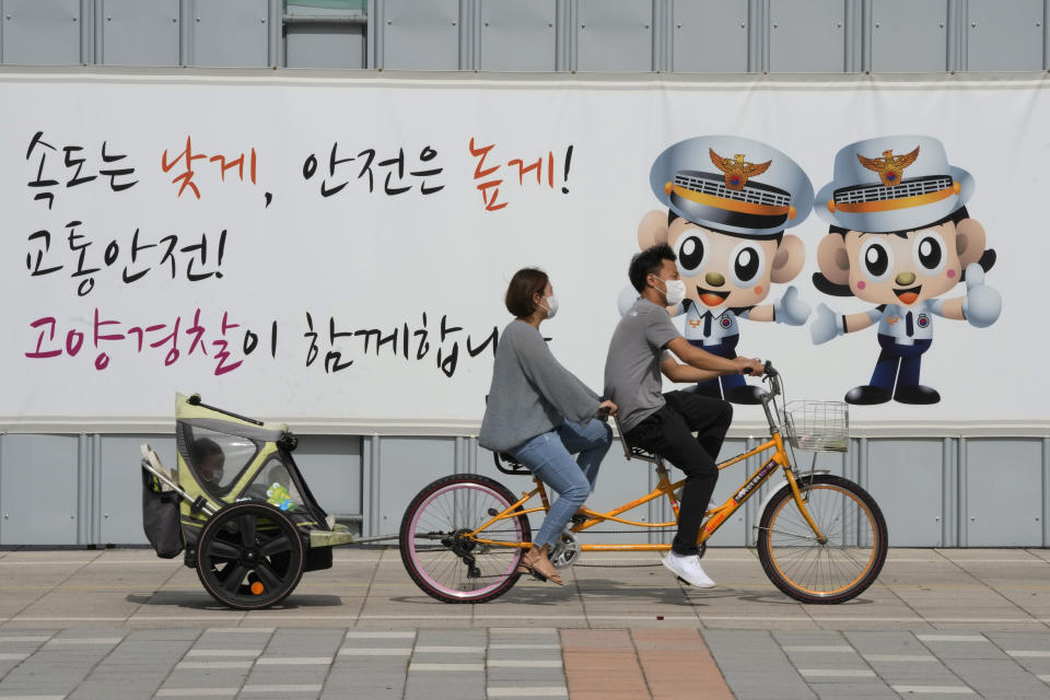 """A couple wearing wearing face masks as a precaution against the coronavirus ride a bicycle with their child at a park in Goyang, South Korea, Sunday, Sept. 5, 2021. The banner reads, """"Traffic safety, Goyang police are with you."""" (AP Photo/Ahn Young-joon)"""