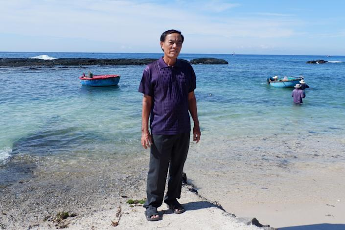 A man stands on the beach in front of a couple of small fishing boats