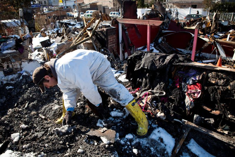 FILE PHOTO: Sylvester searches through remains of his house which was flooded and then burned to the ground during Hurricane Sandy for corpses of his five cats in Midland Beach neighborhood in Staten Island