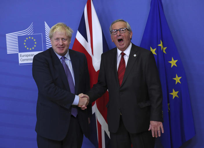 FILE - In this Thursday, Oct. 17, 2019 file photo British Prime Minister Boris Johnson shakes hands with European Commission President Jean-Claude Juncker during a press point at EU headquarters in Brussels. (AP Photo/Francisco Seco)