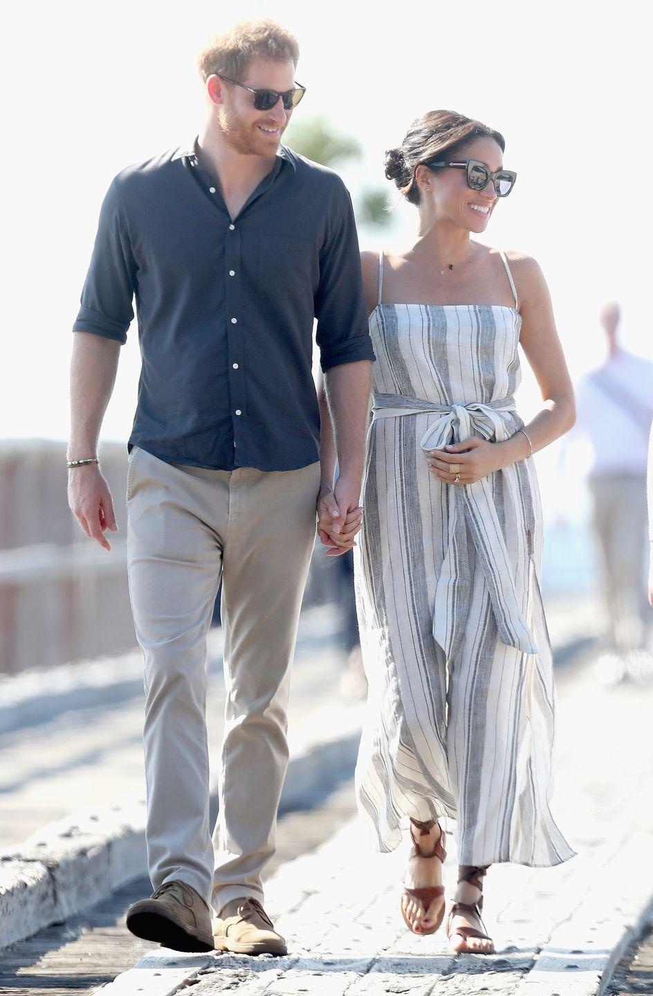 """<p>When she was pregnant with <a href=""""https://www.townandcountrymag.com/society/tradition/g27376121/archie-harrison-mountbatten-windsor-photos-news/"""" rel=""""nofollow noopener"""" target=""""_blank"""" data-ylk=""""slk:Archie"""" class=""""link rapid-noclick-resp"""">Archie</a>, Meghan chose a loose blue and white striped dress with a tie waist. She and Prince Harry chose this summery attire for a visit to Fraser Island, Australia.</p>"""