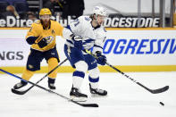 Tampa Bay Lightning center Anthony Cirelli (71) moves the puck in front of Nashville Predators defenseman Ryan Ellis (4) during the first period of an NHL hockey game Tuesday, April 13, 2021, in Nashville, Tenn. (AP Photo/Mark Zaleski)