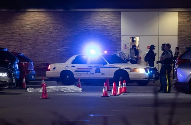 A body is covered with a tarp in the parking lot of the shopping complex after the shooting in Burnaby, B.C., on Thursday. (Darryl Dyck/The Canadian Press - image credit)