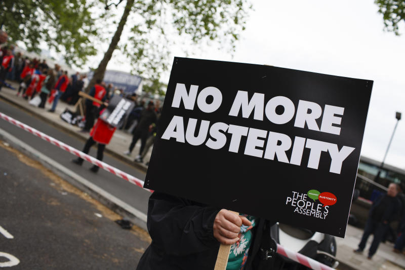 A woman carries an anti-austerity placard as demonstrators calling for fairer pay and rights for workers, as well as against public service cuts and workplace discrimination, gather on Victoria Embankment ahead of the 'New Deal for Working People' march organised by the Trades Union Congress (TUC) in London, England, on May 12, 2018. (Photo by David Cliff/NurPhoto via Getty Images)