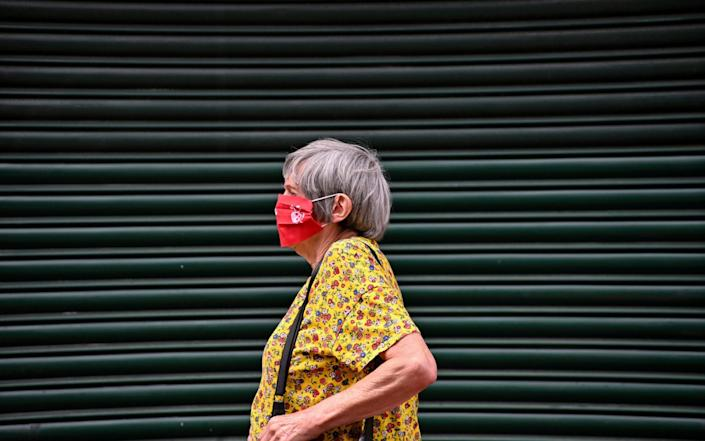 A shopper wears a mask as she walks past shuttered shops in the city centre of Leicester - JUSTIN TALLIS/AFP