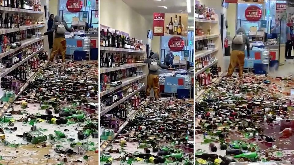 A woman smashes bottles of alcohol at the Aldi.