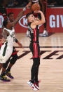Miami Heat guard Tyler Herro (14) shoots as Milwaukee Bucks guard Eric Bledsoe (6) moves in on defense during the first half of an NBA basketball game Thursday, Aug. 6, 2020, in Lake Buena Vista, Fla. (Kim Klement/Pool Photo via AP)