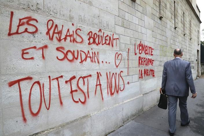 "Graffiti in Paris painted during a demonstration against labour reforms on June 14, 2016 that reads, ""the palaces burn and suddenly...all is ours!"" (AFP Photo/Jacques Demarthon)"