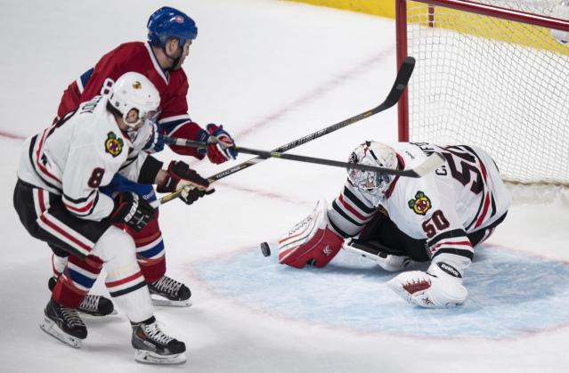 Chicago Blackhawks goalie Corey Crawford blocks a shot by Montreal Canadiens' Brandon Prust as Blackhawks defenseman Nick Leddy defends during the second period of an NHL hockey game, Saturday, Jan. 11, 2014, in Montreal. (AP Photo/The Canadian Press, Paul Chiasson)