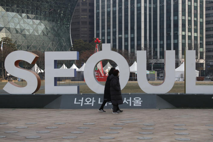 Women wearing face masks as a precaution against the coronavirus walk near the display of South Korea's capital Seoul logo in Seoul, South Korea, Wednesday, Dec. 23, 2020. South Korea has added more than 1,000 new coronavirus cases in a resurgence that is erasing hard-won epidemiological gains and eroding public confidence in the government's ability to handle the outbreak. (AP Photo/Lee Jin-man)