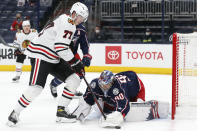 Columbus Blue Jackets' Elvis Merzlikins, right, makes a save against Chicago Blackhawks' Kirby Dach during the first period of an NHL hockey game Saturday, April 10, 2021, in Columbus, Ohio. (AP Photo/Jay LaPrete)