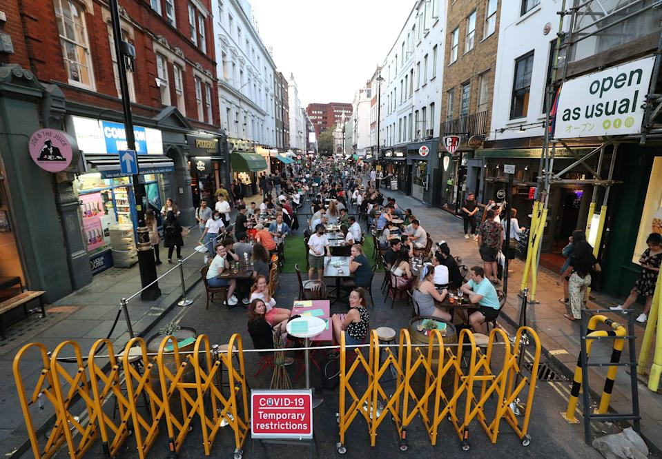People drinking and dining out in Soho, London, as the Metropolitan Police has said it will deploy resources across the capital to enforce the tighter restrictions on social gatherings (PA)