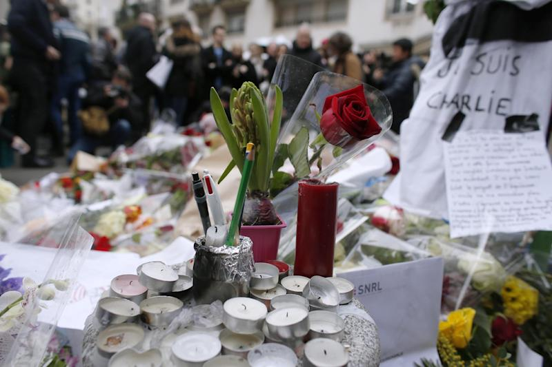 People lay flowers and candles outside of the offices of the French satirical newspaper Charlie Hebdo in Paris on January 10, 2015 (AFP Photo/Thomas Samson)