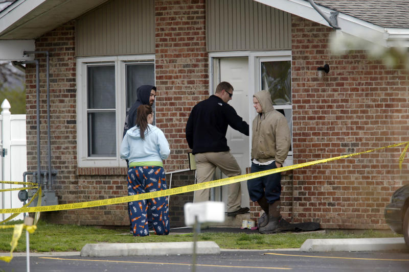 Police officials investigate the scene at a house in Manchester, Ill., where five people were found slain in the tiny southwestern Illinois town early Wednesday, April 24, 2013. Illinois State Police said the suspect died after a car chase and an exchange of gunfire with law enforcement. (AP Photo/The State Journal-Register, Ted Schurter)