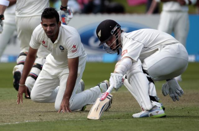 India's Zaheer Khan (L) attempts to field a shot as New Zealand's Kane Williamson makes his ground during day one of the second international test cricket match at the Basin Reserve in Wellington, February 14, 2014. REUTERS/Anthony Phelps (NEW ZEALAND - Tags: SPORT CRICKET)