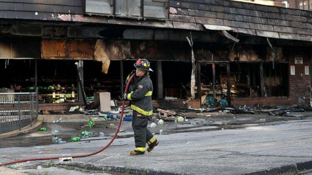 PHOTO: A member of the St. Louis Fire Department removes a hose outside a vandalized and burned convenience store, June 2, 2020, in St. Louis, the morning after protests against the death of George Floyd. (Jeff Roberson/AP)