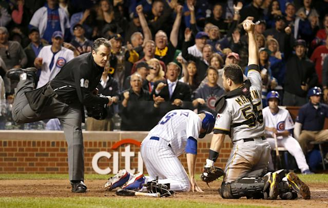 Home plate umpire Mike DiMuro calls Chicago Cubs' Nate Schierholtz out at home as Pittsburgh Pirates catcher Russell Martin shows DiMuro the ball during the ninth inning of a baseball game Monday, Sept. 23, 2013, in Chicago. The Pirates won 2-1. (AP Photo/Charles Rex Arbogast)