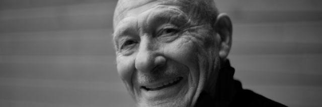 Black and white horizontal capture of handsome happy senior expressing positivity and young soul, playing with camera and laughing