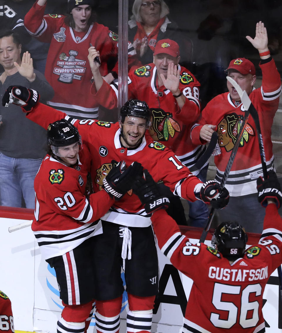 Chicago Blackhawks center Artem Anisimov, center, celebrates with left wing Brandon Saad, left, and defenseman Erik Gustafsson after scoring a goal against the New Jersey Devils during the third period of an NHL hockey game Thursday, Feb. 14, 2019, in Chicago. (AP Photo/Nam Y. Huh)