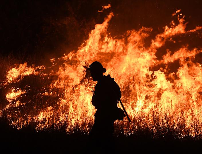 Firefighters conduct a controlled burn to defend houses against flames from the Ranch Fire.