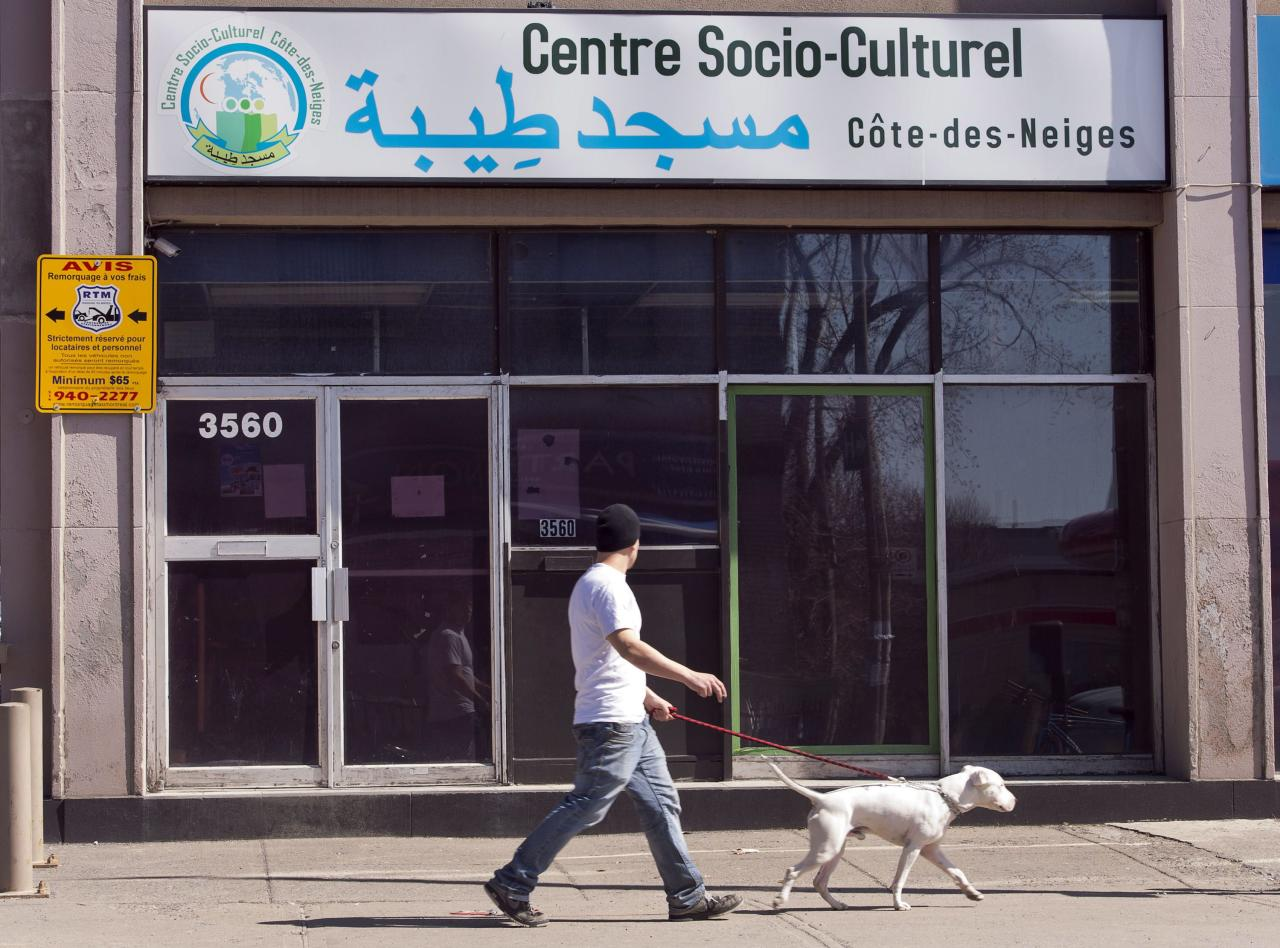 """A man walks his dog past a mosque where Chiheb Esseghaier, one of the two accused in an alleged plot to bomb a Via passenger train, used to attend Tuesday, April 23, 2013 in Montreal. Canadian investigators say Raed Jaser, 35, and his suspected accomplice Chiheb Esseghaier, 30, received """"directions and guidance"""" from members of al-Qaida in Iran. Iran said it had nothing to do with the plot, and groups such as al-Qaida do not share Iran's ideology. (AP Photo/The Canadian Press, Ryan Remiorz)"""