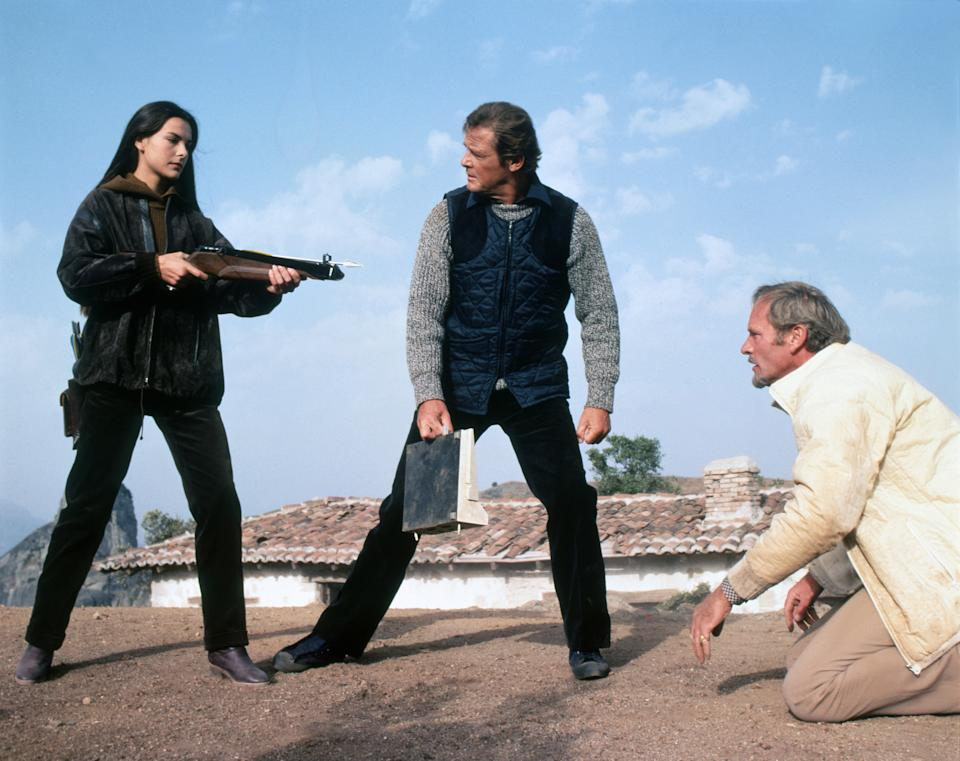 French actress Carole Bouquet, British actors Roger Moore and Julian Glover on the set of For Your Eyes Only, directed by John Glen. (Photo by Sunset Boulevard/Corbis via Getty Images)