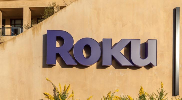 The Roku logo on the side of an office building comprised of sand colored concrete
