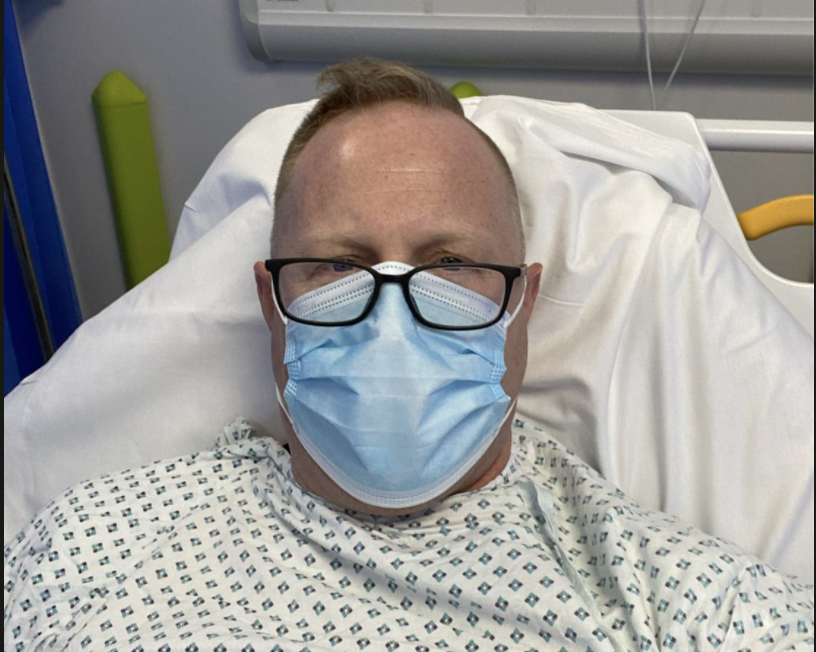 Jonathan Frostick wearing a mask in his hospital bed.