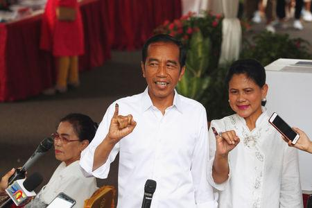 Indonesian President Joko Widodo and first lady Iriana Joko Widodo show their ink-stained fingers after casting their ballots during elections in Jakarta, Indonesia April 17, 2019. REUTERS/Edgar Su