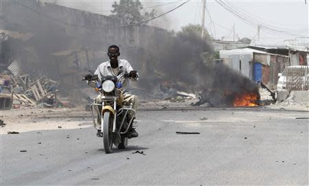 A motorcyclist rides away from the scene of an explosion near the entrance of the airport in Somalia's capital Mogadishu February 13, 2014. REUTERS/Feisal Omar