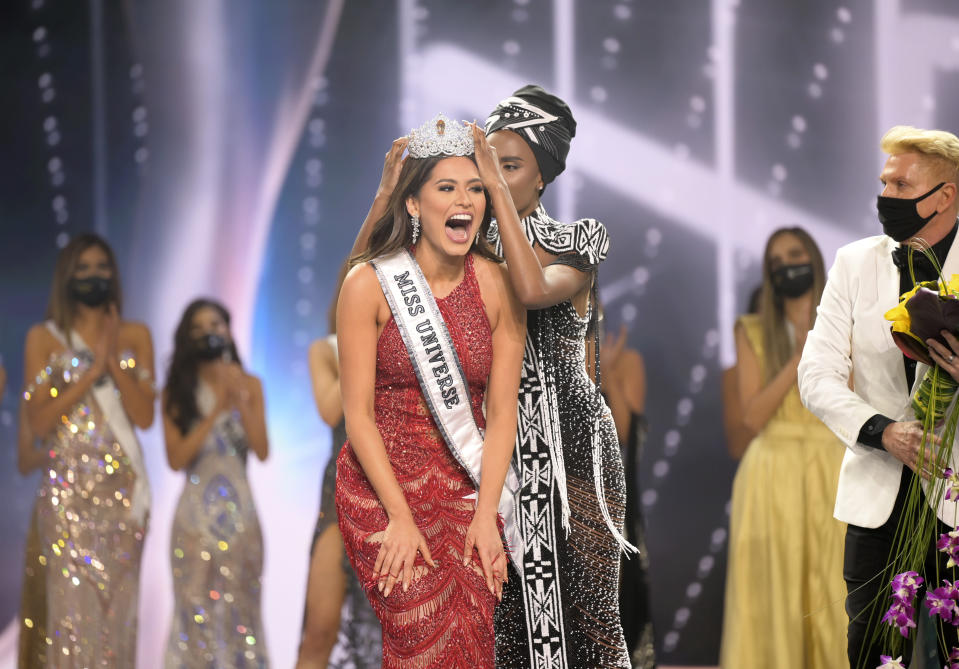 This image released by Miss Universe Organization shows Miss Universe Mexico 2020 Andrea Meza reacts as she is crowned Miss Universe by Miss Universe 2019 Zozibini Tunzi at the 69th Miss Universe Competition at the Seminole Hard Rock Hotel & Casino in Hollywood, Fla. on Sunday, May 16, 2021. (Benjamin Askinas/Miss Universe via AP)